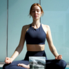 Woman sitting cross legged in yoga activewear, with protein powder bag in front