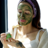 Christina with clean greens facemask on her face and holding mask jar