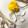 clear quartz crystals next to yellow and light purple flowers