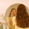Woman using serum on her face, looking in circle mirror