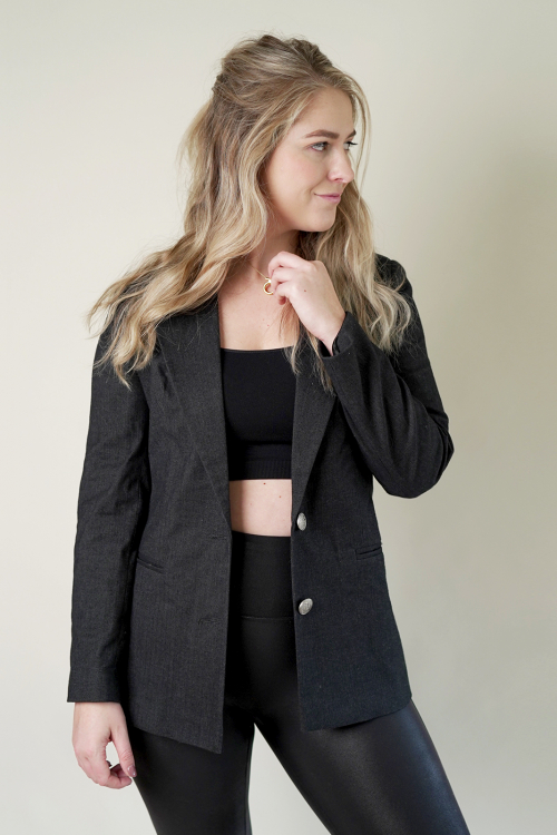 Female blonde model wearing dark grey wool blazer with two silver buttons. Blazer open styled with black sports bra and black leggings.