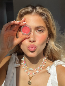 Model holding lip to cheek product over eye with pursed lips