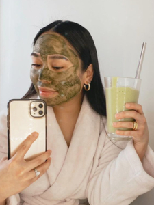 Woman with clean greens facemask on, holding green smoothie, and taking a selfie in mirror