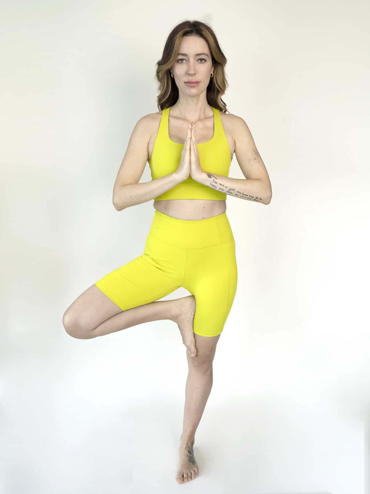 Female wearing Chartreuse sports bra and biker short set in tree pose