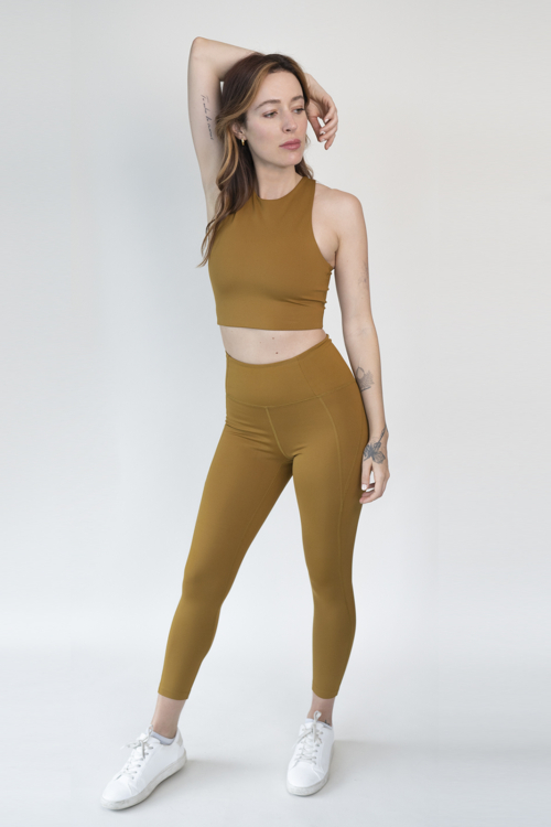 Christina wearing Saddle burnt yellow bronze colored Dylan Sports Bra and High Rise Compressive leggings